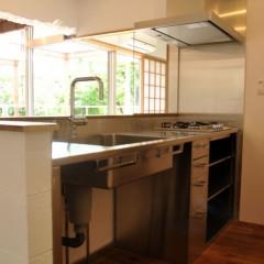 ステンレスで造作したキッチン。リビングの向うに敷地内の豊かな緑が見えます。