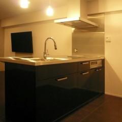 キッチン面材はブラックの鏡面仕上げ。カウンターは厚みのあるステンレスです。