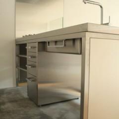 シンク下はダストボックス等が置けるようオープンスペースに。床はモルタル仕上げです。