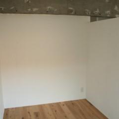 リビング横の寝室エリア。右側の壁は天井との間に空間を設けています。