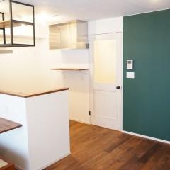 グリーンの壁の横にはヴィンテージ風の塗装を施したドア。