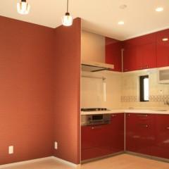 施主さまセレクトのキッチンとクロス。濃い赤が意外とシックに決まっています。