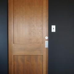 キッチンの後ろはパウダールーム。黒の塗装と木製のドアがインテリアを引き締めています。