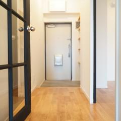 リビングのガラス格子の扉の向こうは廊下。そして玄関に続きます。