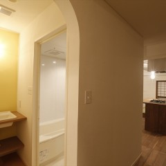 木のカウンターに洗面器を埋め込む形にしています。壁は優しいレモンイエロー。