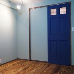 寝室です。鮮やかな水色の壁と、爽やかなブルーのドア。