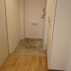 玄関です。シューズクロークの扉なども白で統一しています。土間はモルタル仕上げに。