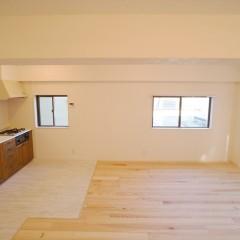 キッチンスペースの床材のみ白のヴィンテージ加工風のフロアタイルでゾーニング。