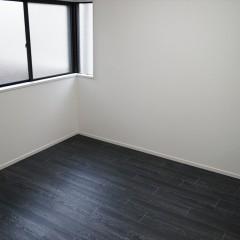 玄関を入って右手の寝室です。こちらはシンプルに黒のフローリング+白の壁。