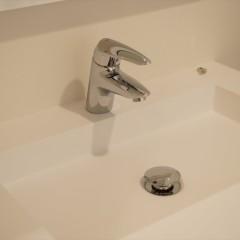 スクエアな形の壁付けの洗面台にグローエの水栓。シンプルかつスタイリッシュに。