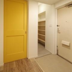 大きな土間から見える子供部屋への入り口はイエローに塗装。