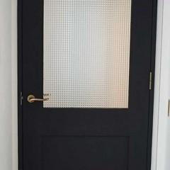 真っ白な家を引き締める、黒塗装したリビングドア。