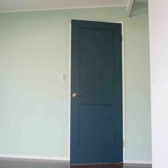 淡いグリーンの塗装にネイビーのドア。