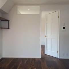 リビングと寝室がさりげなく繋がるよう、高さ目いっぱいに造作した窓。