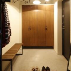 シンプルな玄関を彩るのは、ハンガーラック、スタンドミラー、照明。