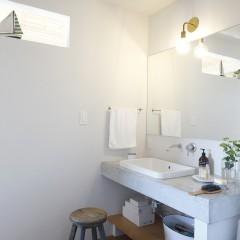 十分な広さでシンプルに仕上げた洗面台はモルタルと木で造作。