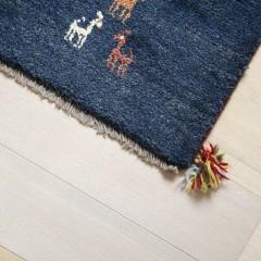 ベッドの足元には、シーツの色と統一されたギャベのラグ。