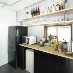 収納棚はメラミン材で造作。天板とオープン棚を木で合わせ、黒を和らげた。
