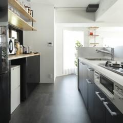 再利用のキッチン扉は黒いシート貼りで印象を変え、床も合せて黒いフロアタイルを貼った。