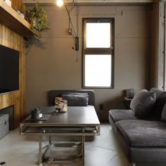 テレビ下のニッチには季節物をトランクに入れ収納。ローテーブルは黒皮鉄で造作。