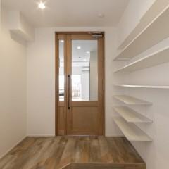 玄関からリビングへ奥行を感じられるよう、大きなガラス入りの親子ドアを造作。